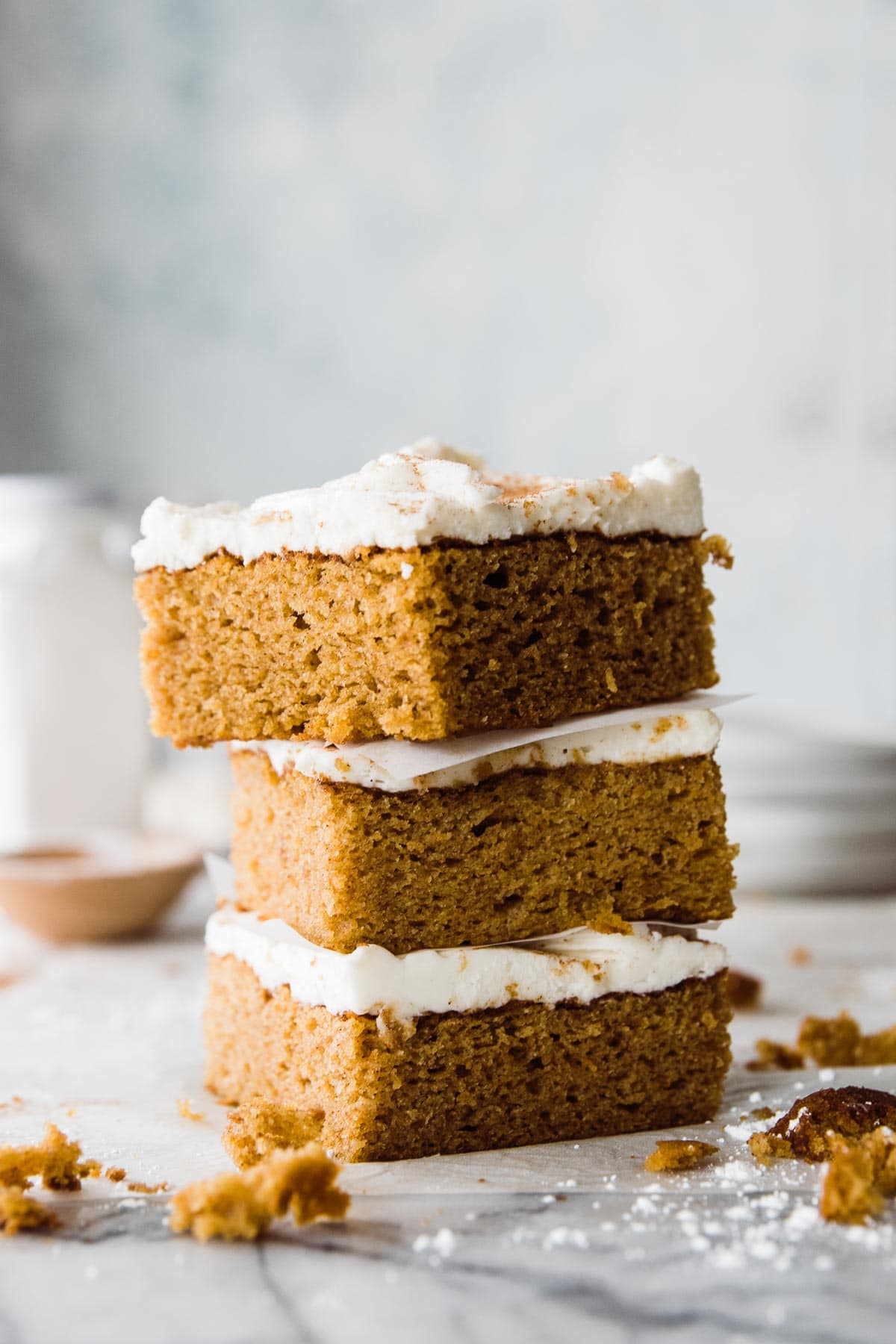 three pieces of fluffy frosted  pumpkin cake stacked on top of each other