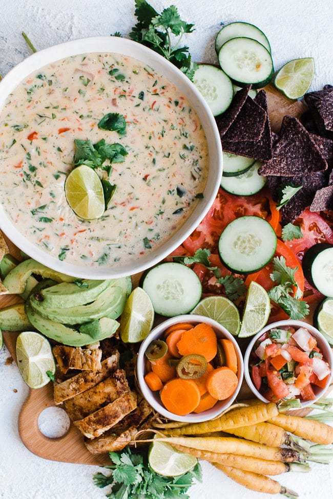 Queso Blanco Mexican White Cheese Dip on a wooden cutting board with chips, veggies, and chicken.