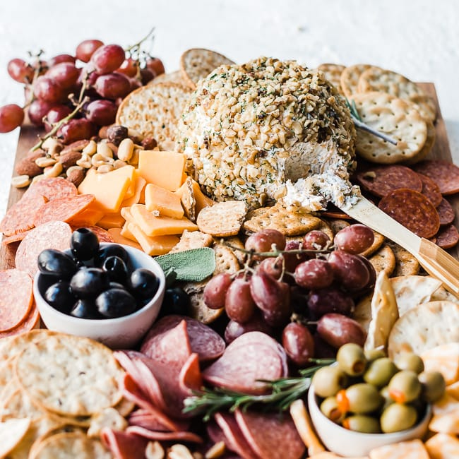 Ranch cheeseball recipe on a wooden cutting board with crackers, nuts, olives, grapes, and meats.