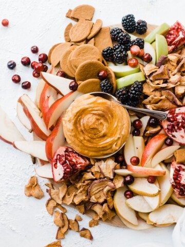 Pumpkin pie dip on a wooden cutting board with apples, pears, and berries.