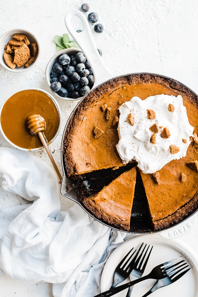 Pumpkin pie with gingersnap crust in a cast iron pan with blueberries to the side.