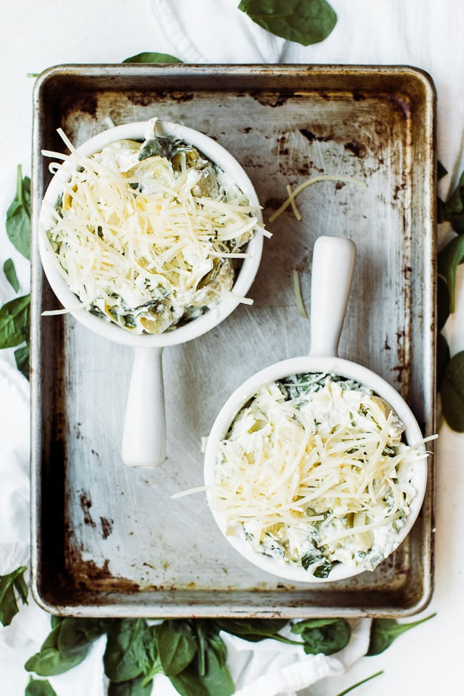 two bowls of spinach artichoke dip with cheese on top