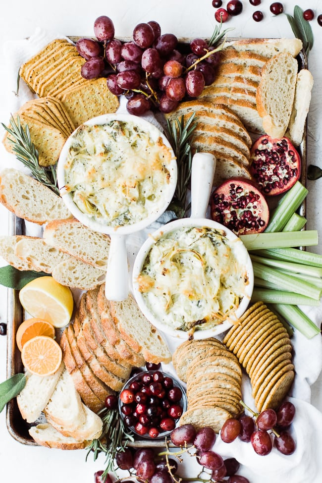 spinach artichoke dip with bread, crackers around it
