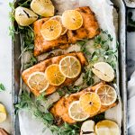 Citrus salmon in a metal sheet pan, it is surrounded by greens and garnished with citrus slices.