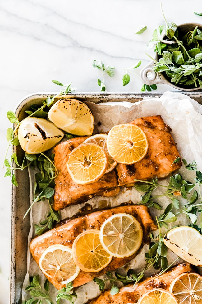 A closeup of citrus salmon on a baking tray, The salmon has citrus slices on top of it, and lemon slices to the side.