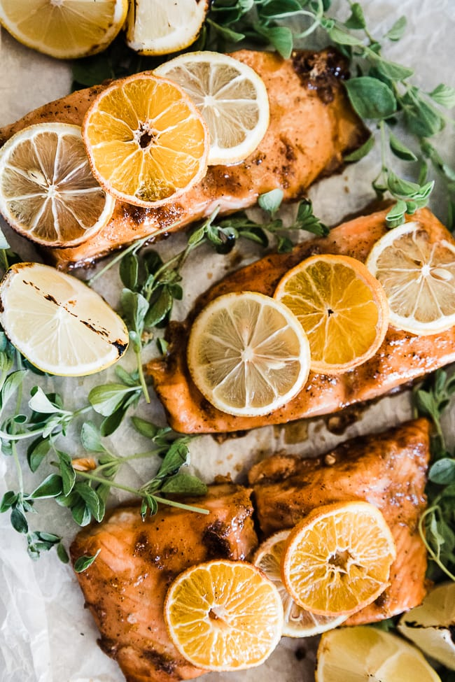 A closeup of citrus salmon on a baking tray, The salmon has citrus slices on top of it.