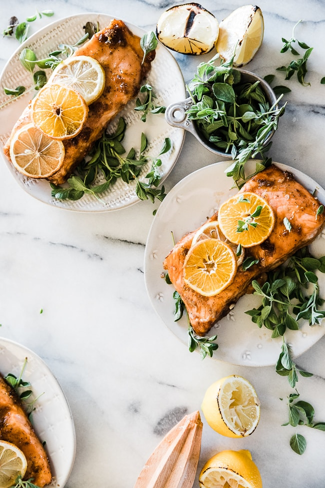 Citrus salmon on white plates, garnished with lemon slices and thyme.