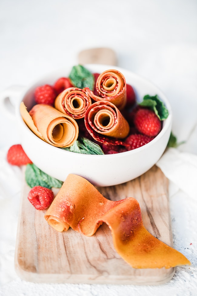 Homemade peach and raspberry fruit leather in a white bowl with fresh raspberries.