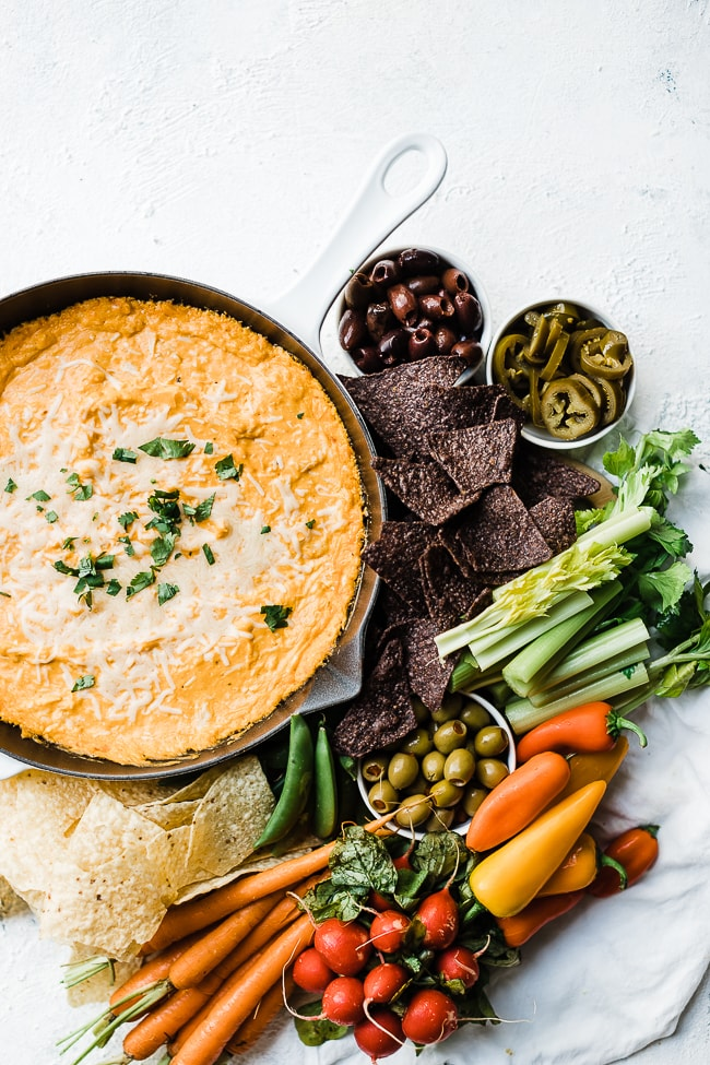 Hot buffalo chicken dip in a white cast iron skillet, surrounded by tortilla chips and fresh veggies.