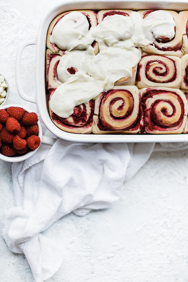 raspberry sweet rolls being frosted.