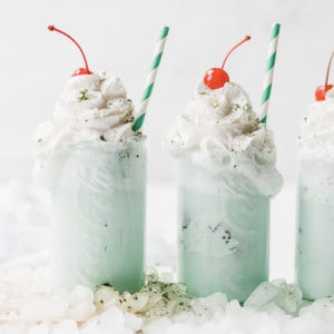 Ice cream soda recipe in glass glasses, topped with whipped cream and a cherry.