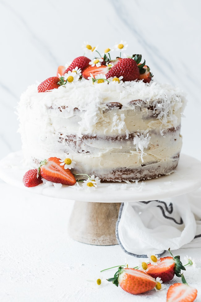 Coconut Strawberry Cake on a marble cake stand. Garnished with strawberries and white flowers.
