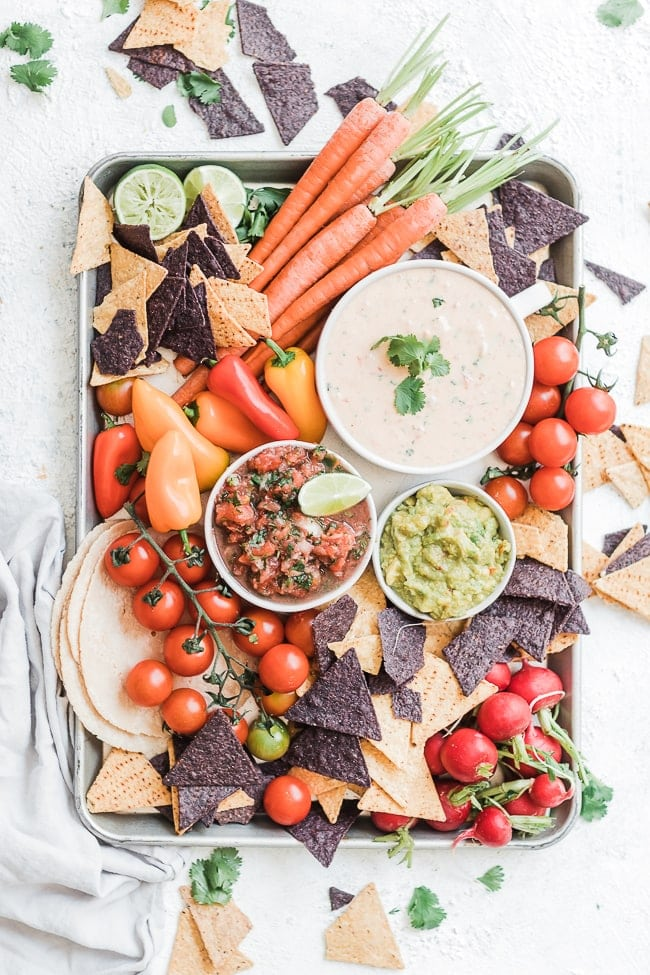 easy queso dip on a sheet pan surrounded by carrots, tomatoes, salsa, guacamole, and chips.