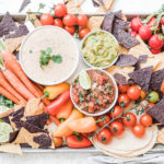 easy quest dip on a sheet pan surrounded by carrots, tomatoes, salsa, guacamole, and chips.