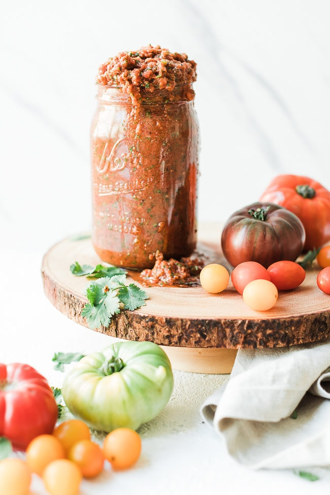 Chipotle salsa recipe in a mason jar, atop a wooden cake stand, surrounded by tomatoes.