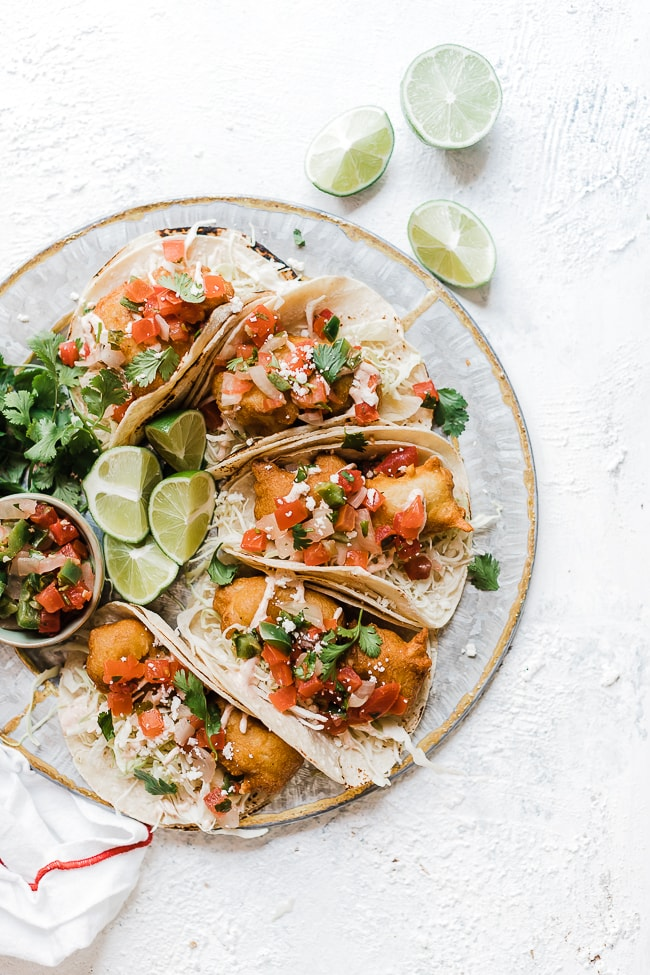 Battered fish tacos on a round platter. Garnished with limes and cilantro.