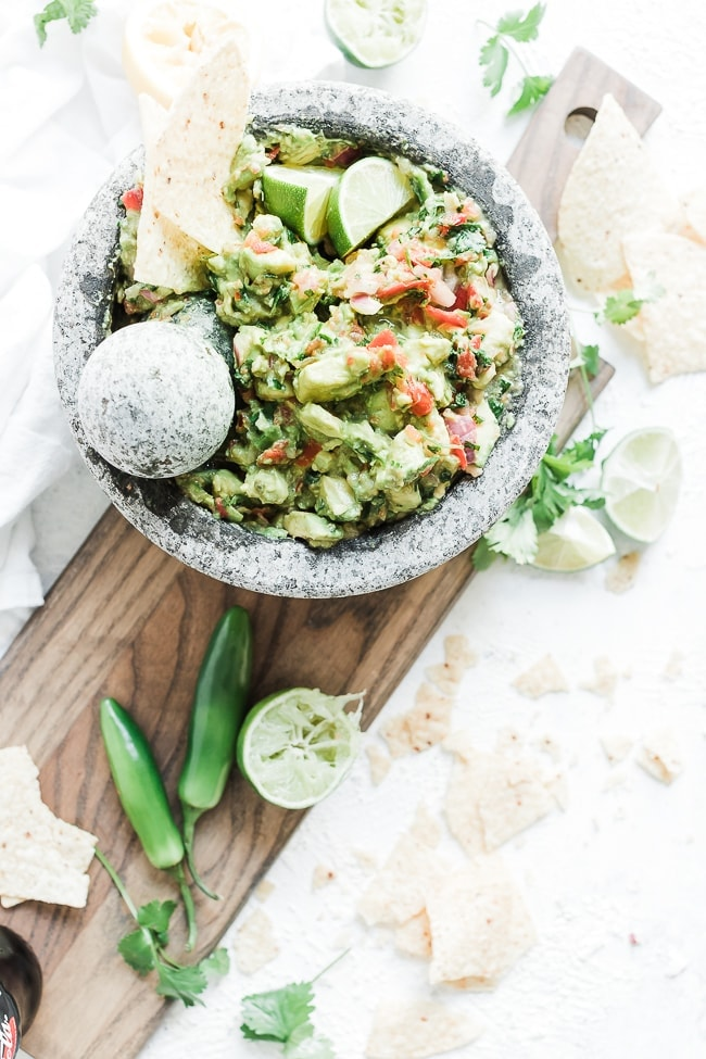 Healthy guacamole in a concrete bowl, on top of a cutting board.