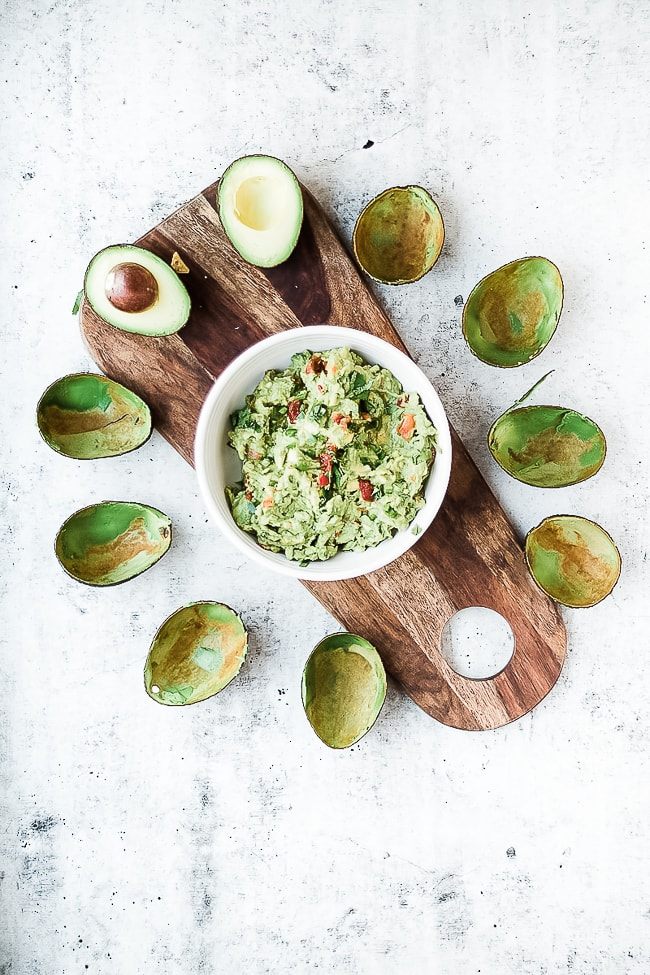 Healthy guacamole recipe in a bowl, surrounded by avocado peels in the shape of a flower.