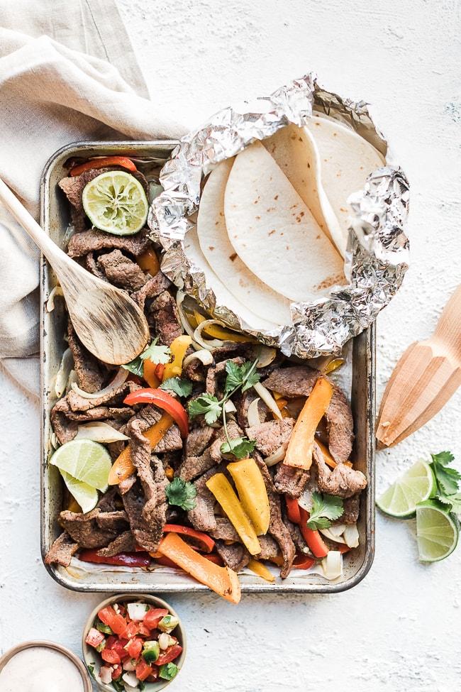 Sheet pan steak fajitas on a silver sheet pan with a grey napkin.