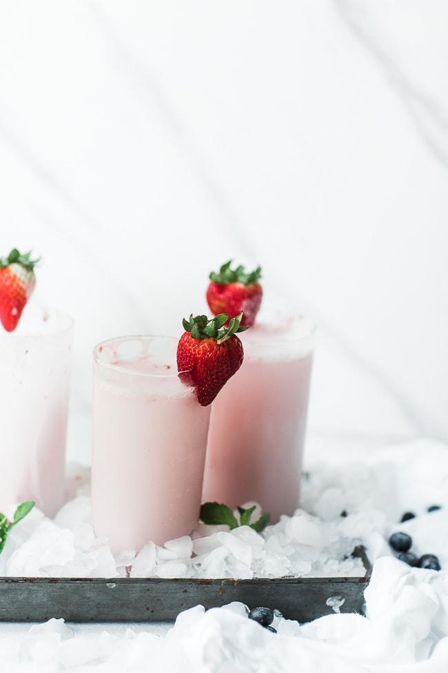 Cream Soda Recipe in glasses, garnished with a strawberry.