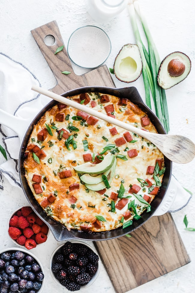 Ham & egg casserole in a cast iron skillet. - surrounded by berries.