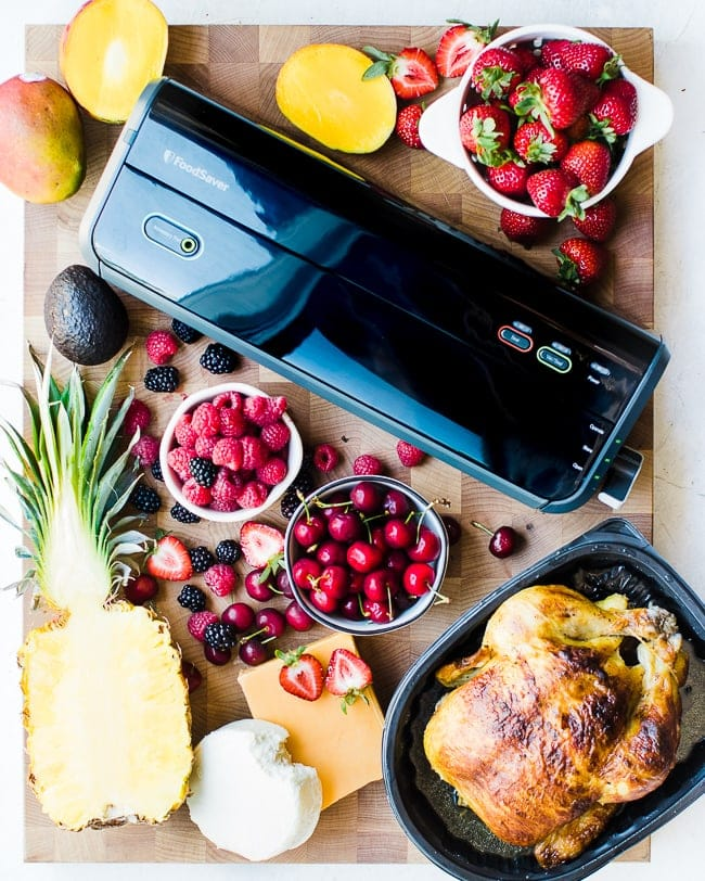 Foodsaver with fruits, cheese, and meat on cutting board