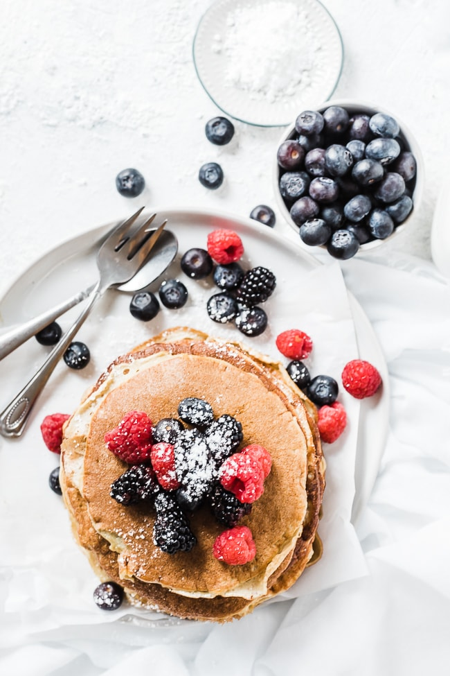 Healthy protein pancakes on a white plate - garnished with berries and powdered sugar.