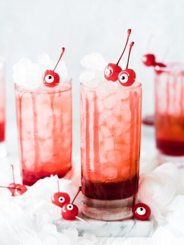 two cups full of ice, pink drink with red syrup at the bottom and two cherry eyeballs