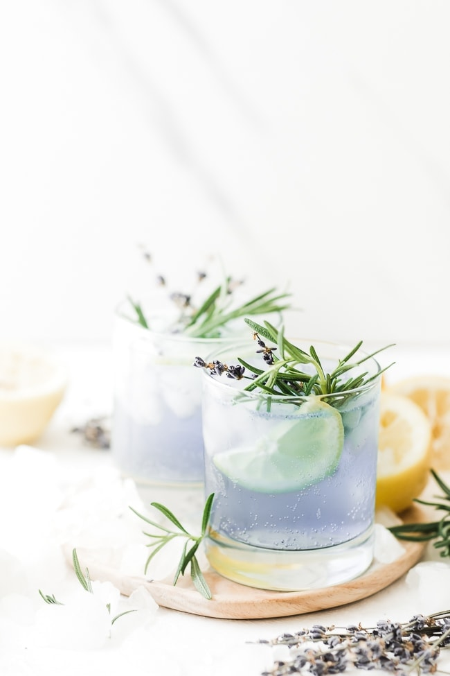 Sparkling lavender lemonade in glass glasses, surrounded by lemons.