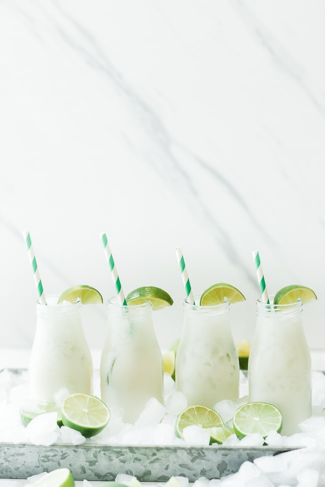 Brazilian limeade in milk glasses, garnished with lime.