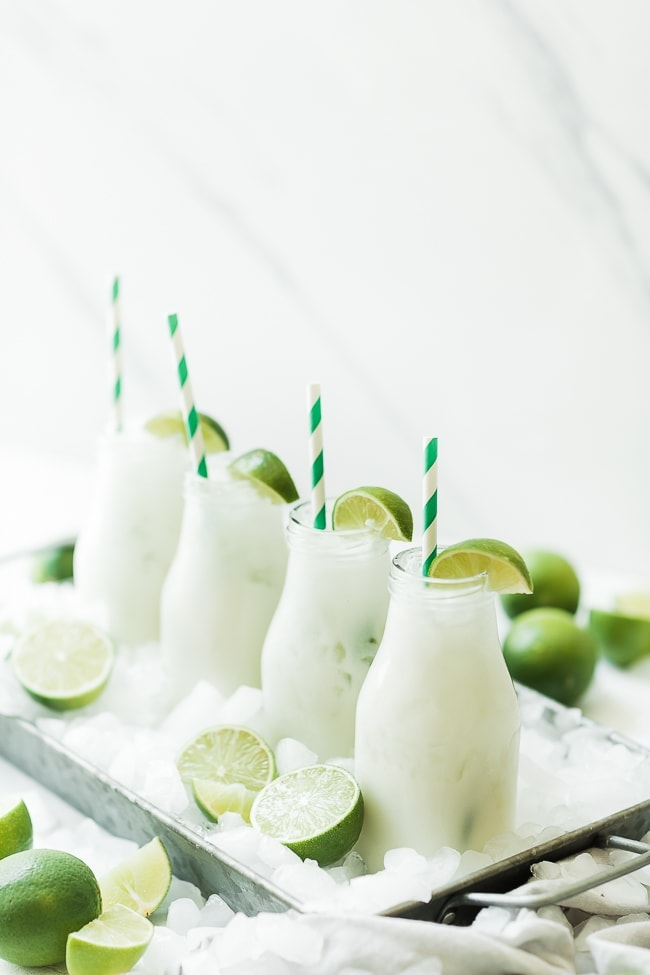 Limeade lined up in milk glasses.