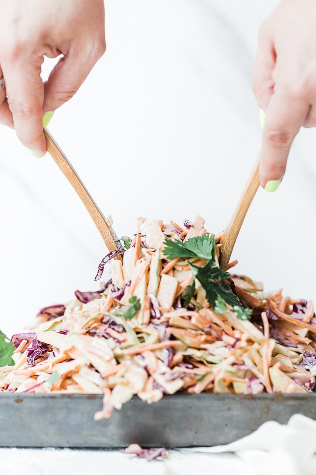 Country coleslaw being tossed.
