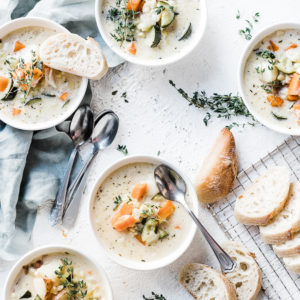 Summer corn chowder in white bowls, aside sliced bread, and garnished with thyme.