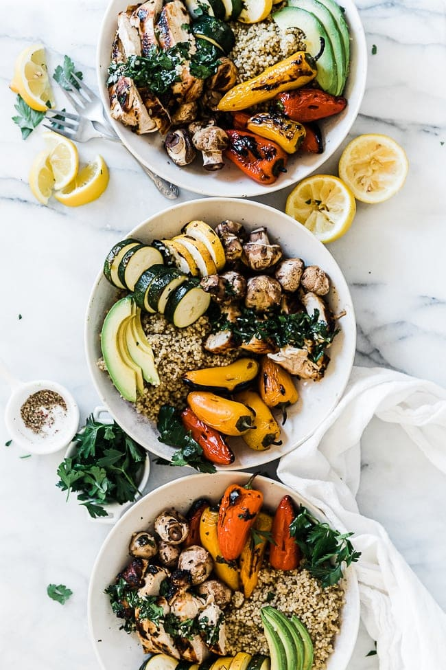 Three white bowls lined up filled with Chimichurri chicken and veggies.