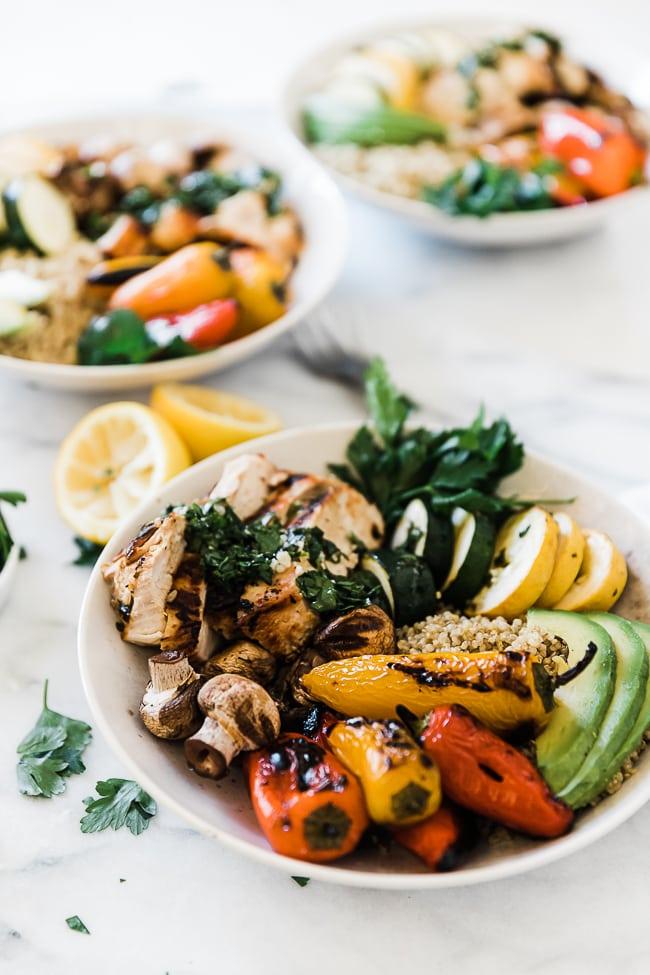 A 3/4 view Chimichurri chicken veggie bowl in white bowls.