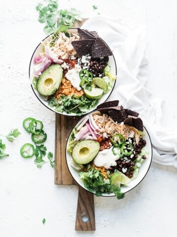 Chicken burrito bowl recipe in black rimmed bowls atop a wooden cutting board.