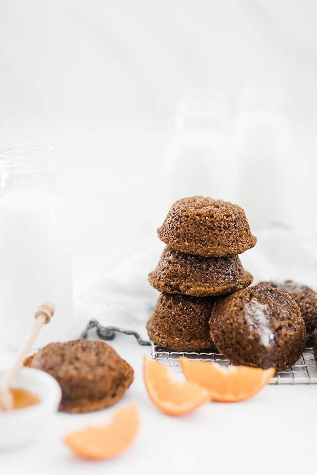 Molasses bran muffins stacked on a cooling rack, next to milk in bottles.