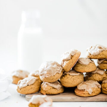Soft pumpkin cookies stacked on a wooden cutting board.