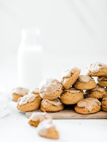 Soft pumpkin cookies on a wooden cutting board, next to a glass of milk.