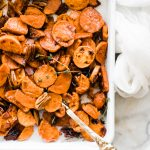 sweet potatoes baked on white baking sheet with cold spatula