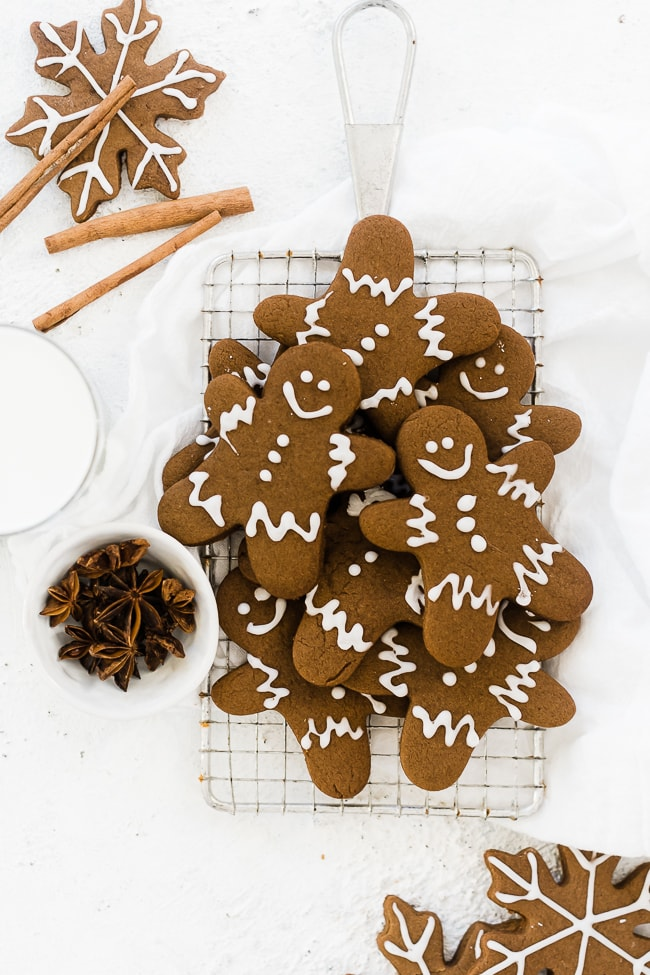 Easy gingerbread men recipe on a cooling rack, next to cinnamon sticks and star anis.