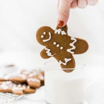 Easy gingerbread men recipe being dipped into a glass of milk.