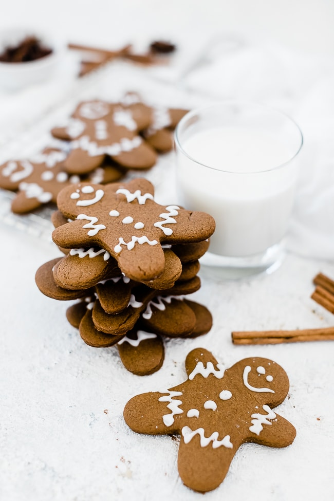 Easy gingerbread men recipe stacked next to a glass of milk.
