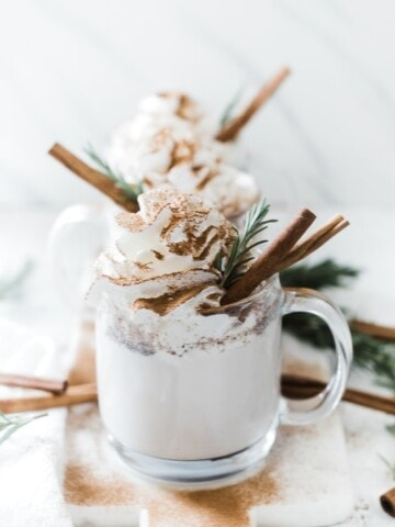 Pressure cooker warm milk and cinnamon in glass mugs, topped with whipped cream and garnished with rosemary and a cinnamon stick.