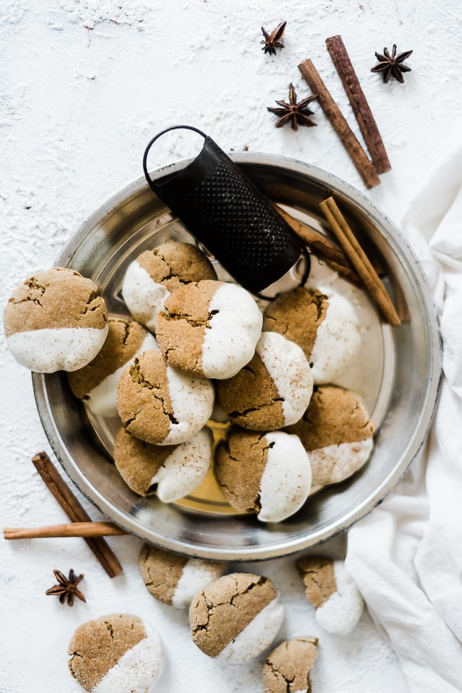 Soft molasses cookies in a pie tin, garnished with cinnamon sticks.