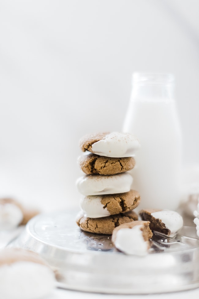 Soft molasses cookies, stacked, next to a glass of milk.