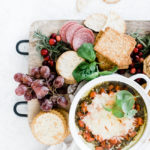 cream cheese pesto dip on a cheese board surrounded by crackers, grapes, and salami.