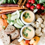 Cheddar cheese fondue recipe in two white mugs, surrounded by bread and veggies on a wooden cutting board.