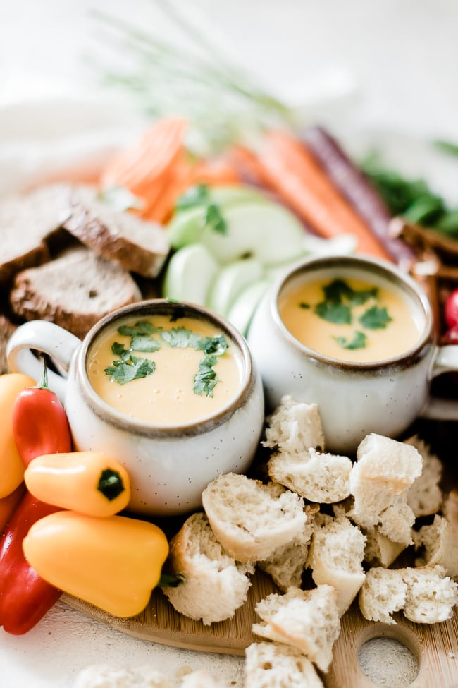 Cheddar cheese fondue recipe in two white mugs, surrounded by bread and veggies.