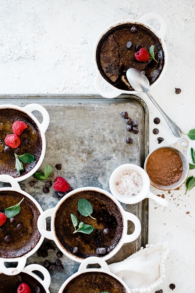 Chocolate creme brûlée arranged on a baking tray on white tart dishes.